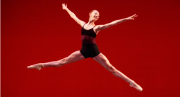 A female dancer performs a jump.