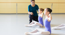 An instructor works with three young dancers.