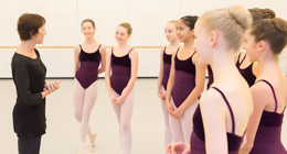 An instructor addresses a group of young dance students in the studio.