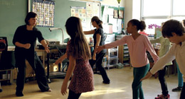 A dance instructor leads a dance class in a public school classroom.