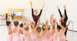 An instructor leads a group of young dancers.