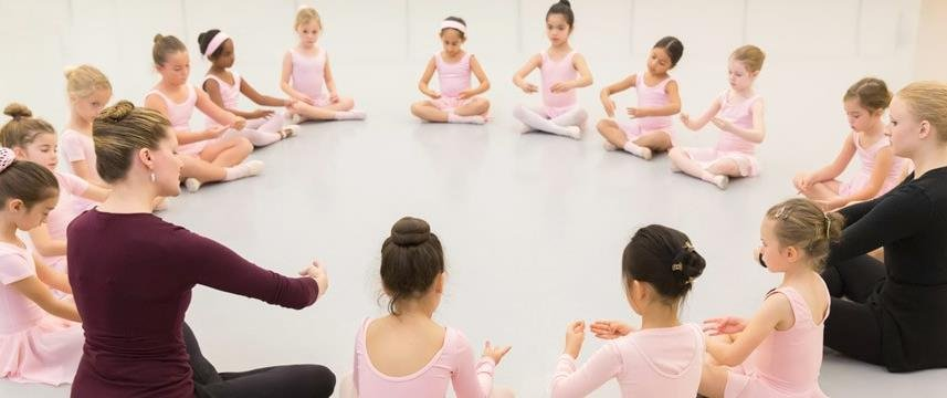 A group of young dancers sit in a circle during a class.