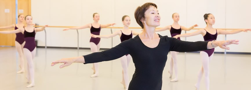 An instructor leads a class of dancers.