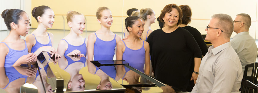 A class of dancers gather around a dance accompanist at the piano.