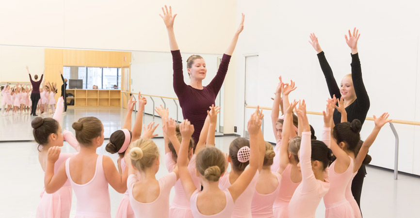 Instructors lead a group of young dancers.