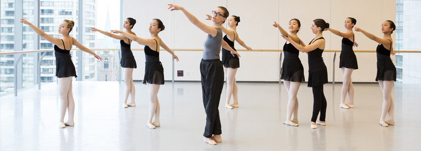 A class of dancers follow their instructor.