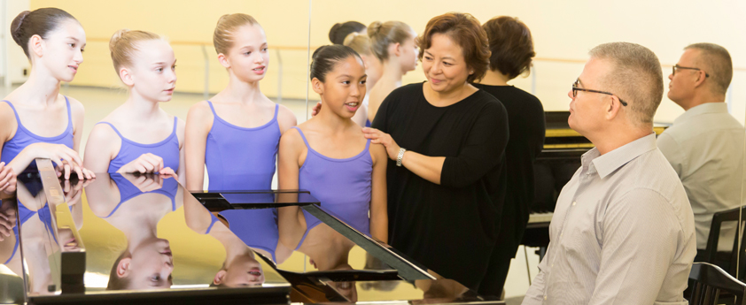 A class of students observe a student receiving instruction at the barre.