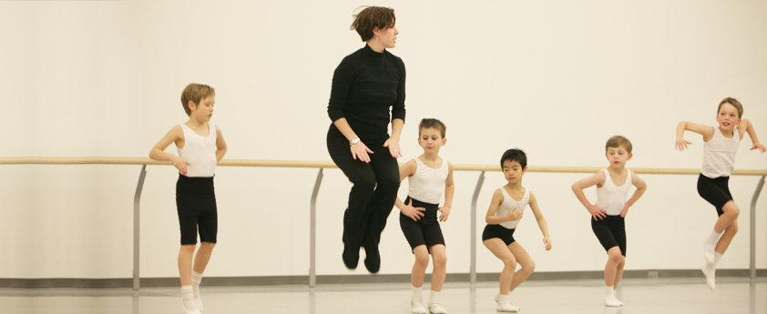 Five dance students practice at the barre while their instructor assists one of them.
