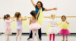 woman instructs class of young dancers